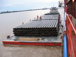 Charter ship discharging pipe onto barge for project